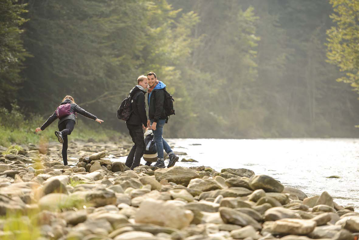 Jugendliche an einem Fluss im Wald.