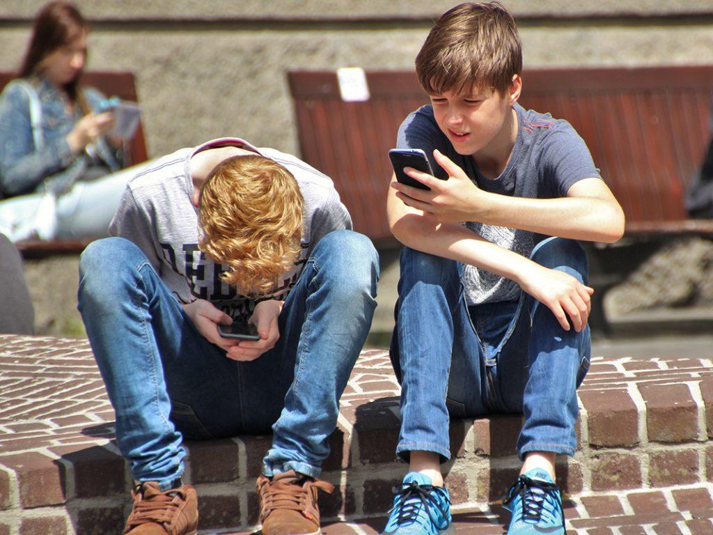 Zwei Kinder sitzen auf dem Boden und nutzen ihre Smartphones