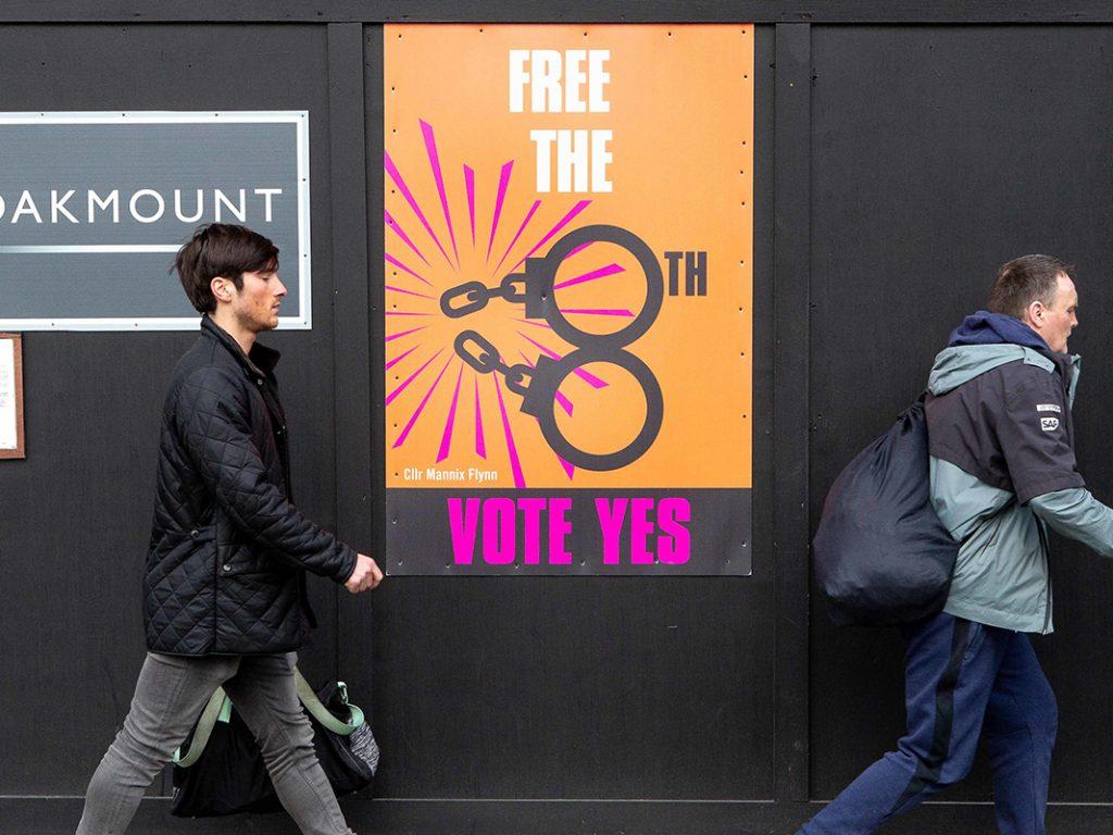 Passanten gehen an einem Plakat vorbei, auf dem dafür geworben wird, beim Referendum für die Abschaffung des Verfassungszusatzes zum Abtreibungsverbot zu stimmen.