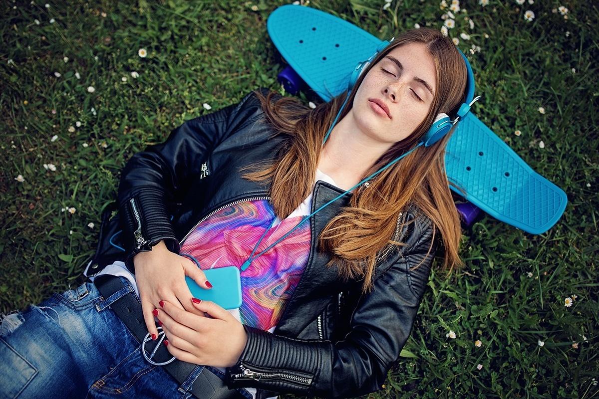 Ein Teenager liegt auf dem Skateboard und hört Musik mit Kopfhörern