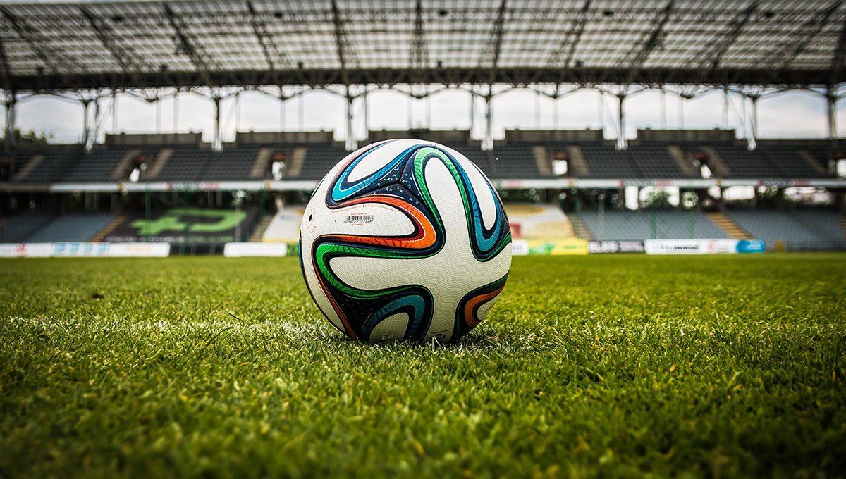 Ein Fußball inmitten eines Stadionplatzes