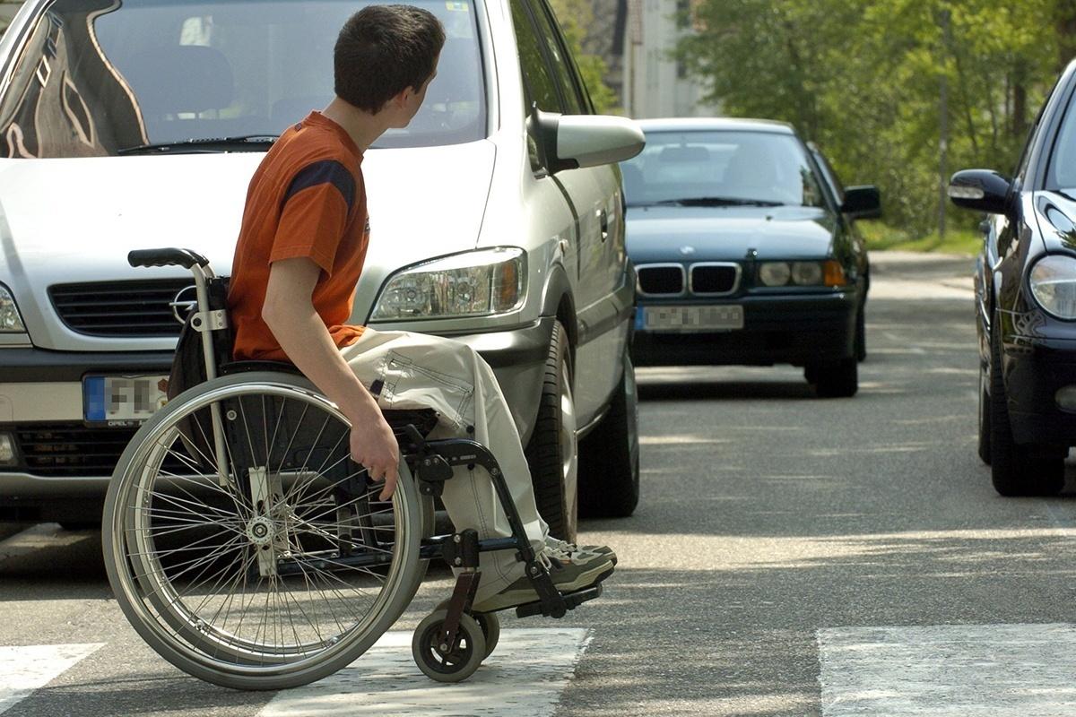 Ein Rollstuhlfahrer fährt über einen Zebrastreifen