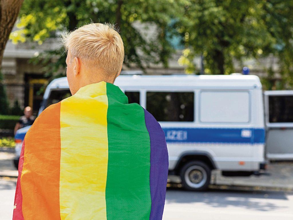 Demonstrant mit Regenbogenflagge