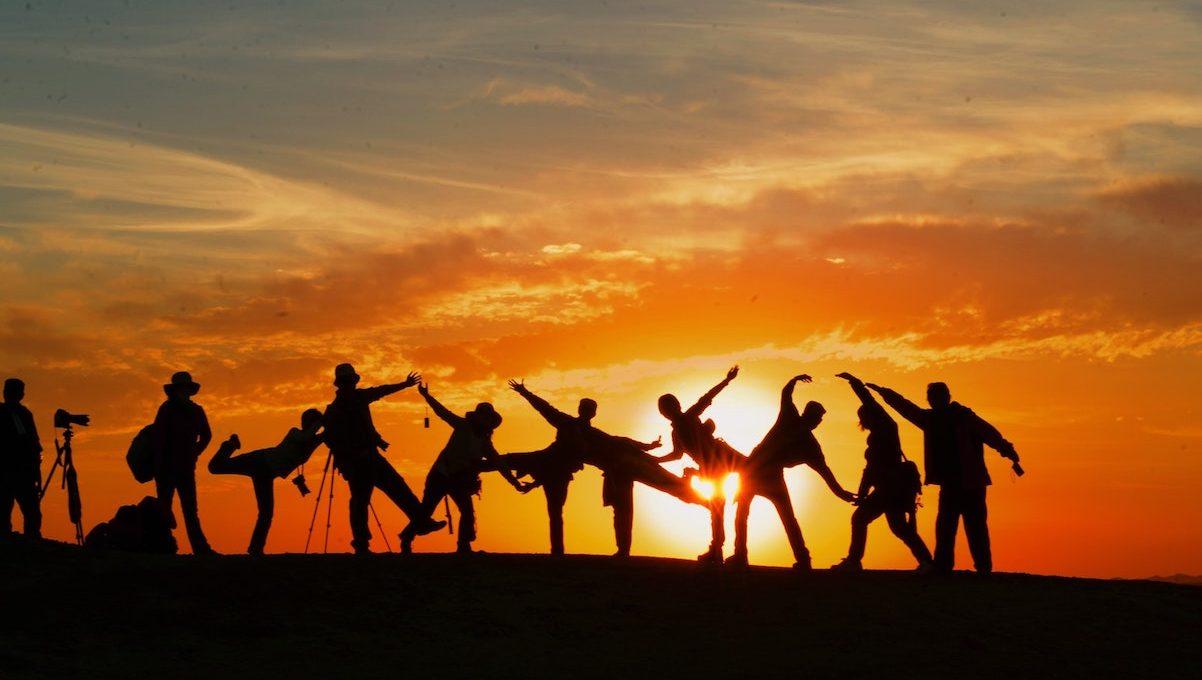 Gruppe von Menschen vor Sonnenuntergang