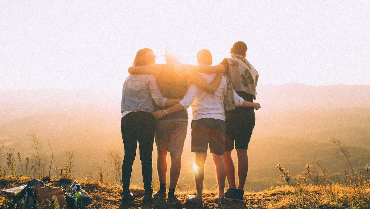 Vier junge Leute schauen in den Sonnenuntergang.