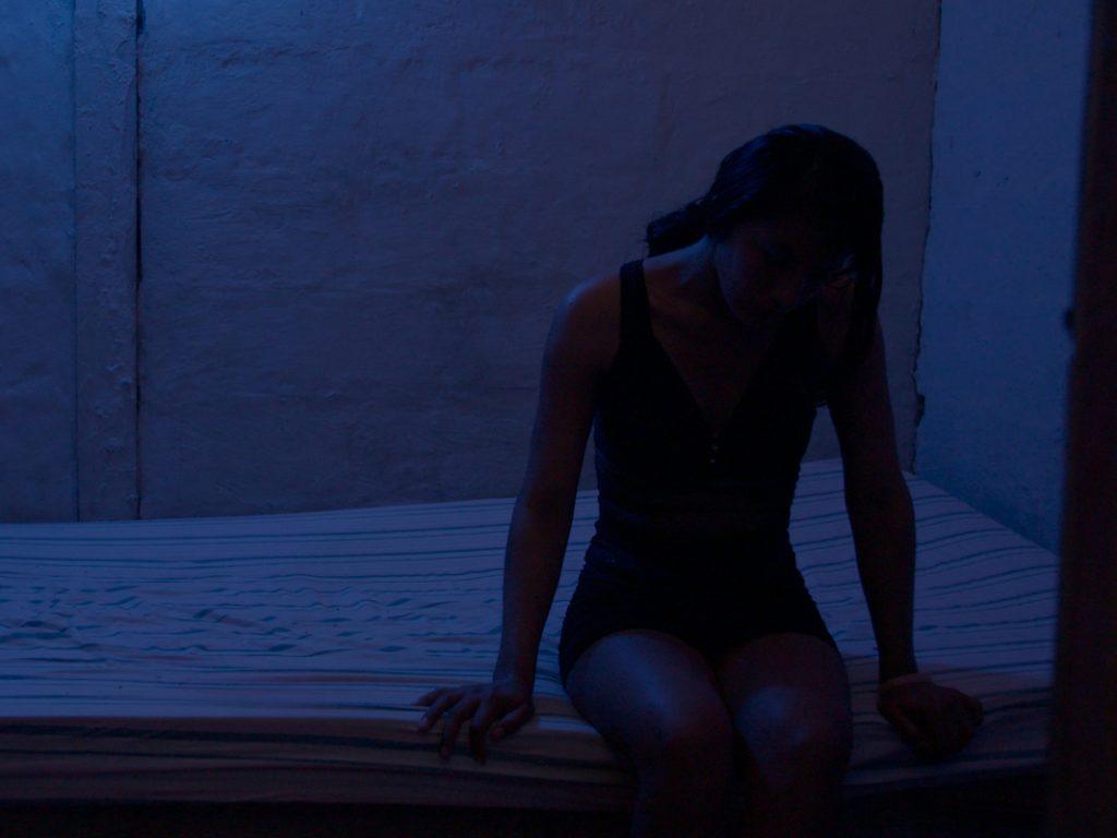 Eine junge Frau sitzt auf einer Matratze