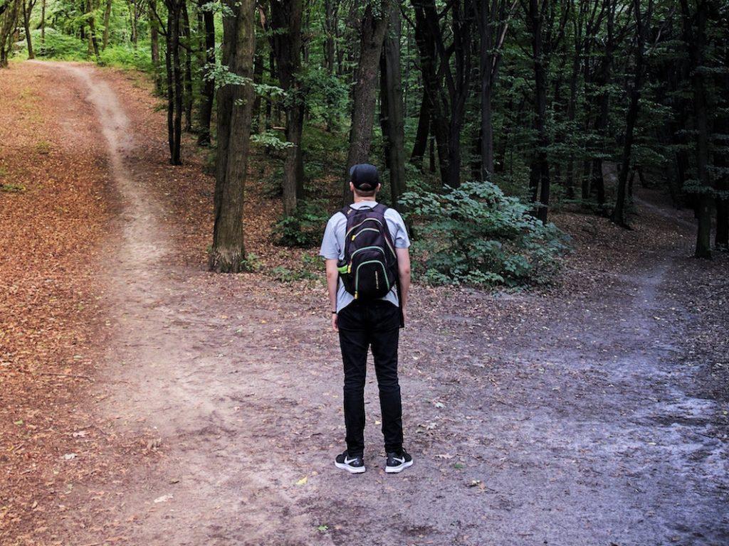 Ein Mann im Wald, der vor Kreuzweg steht