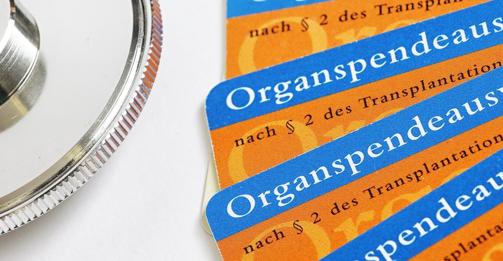 Paar Organspende-Ausweise neben einem Stethoskop