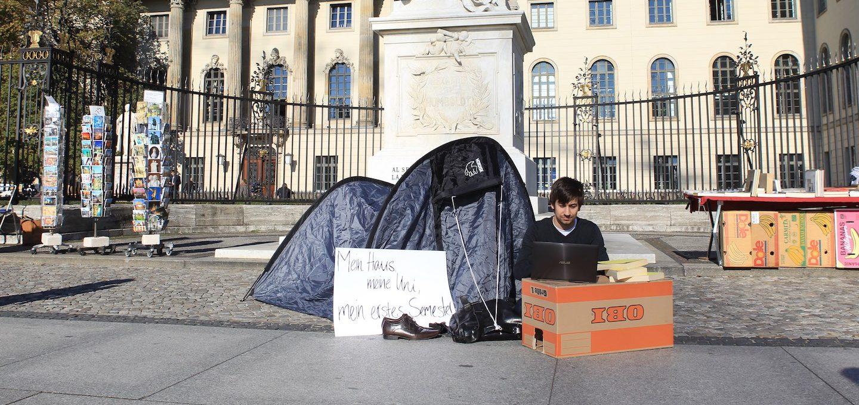 Ein Mann sitzt mit einem Karton, Zelt und Laptop vor einem Gebäude