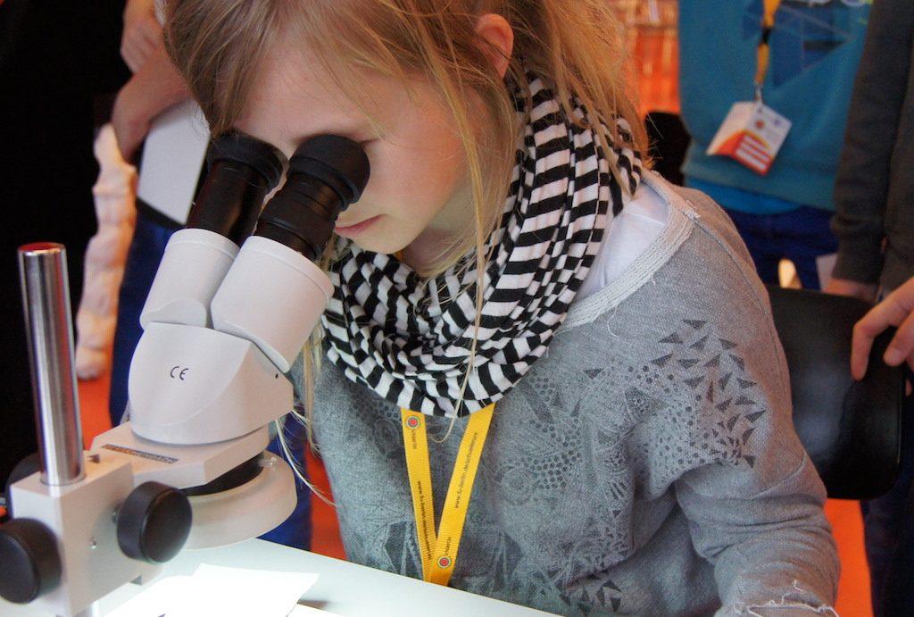 Mädchen schaut durch Mikroskop