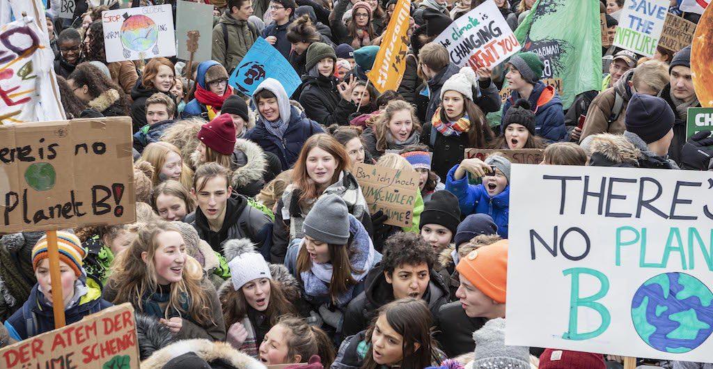 Schüler demonstrieren und halten Schilder hoch
