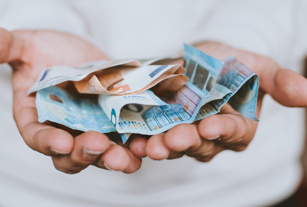 Zwei Hände und Euro-Geldscheine.