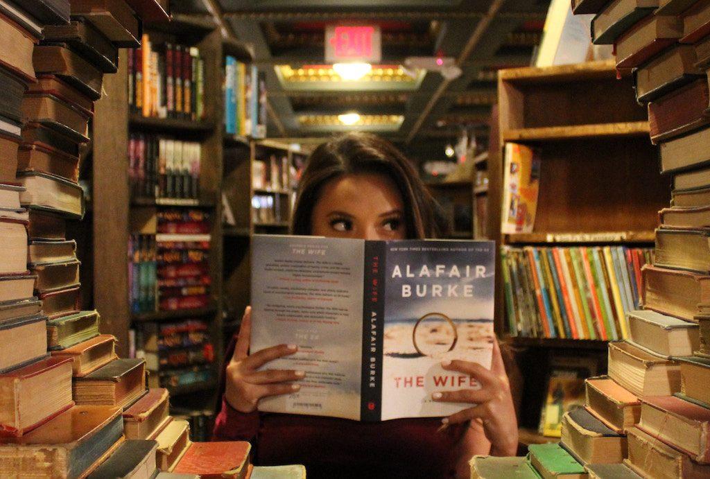 Mädchen liest ein Buch neben Stapeln von Büchern
