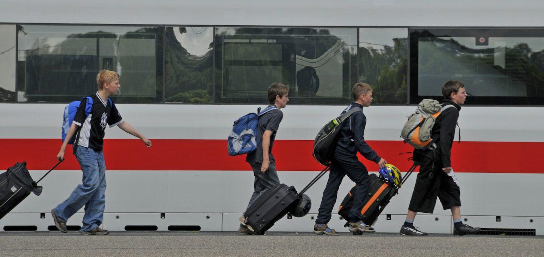 Schüler gehen an einem ICE den Bahnsteig entlang.