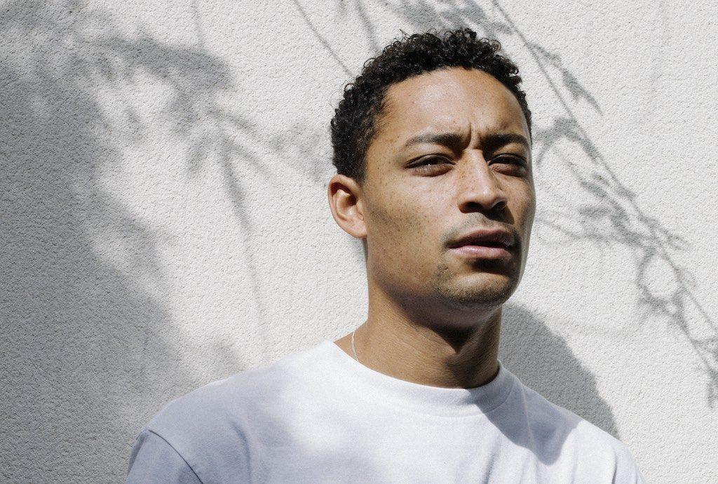 Der Rapper Loyle Carner vor weißer Wand fotografiert.
