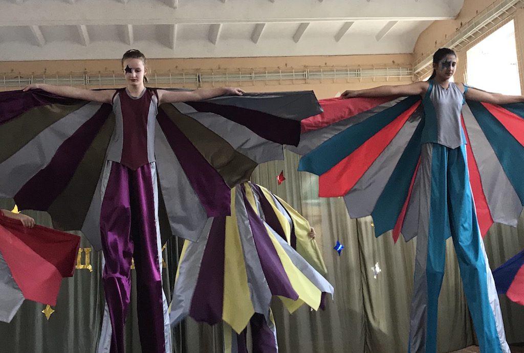 Schüler mit bunten Kostümen tanzen auf Stelzen
