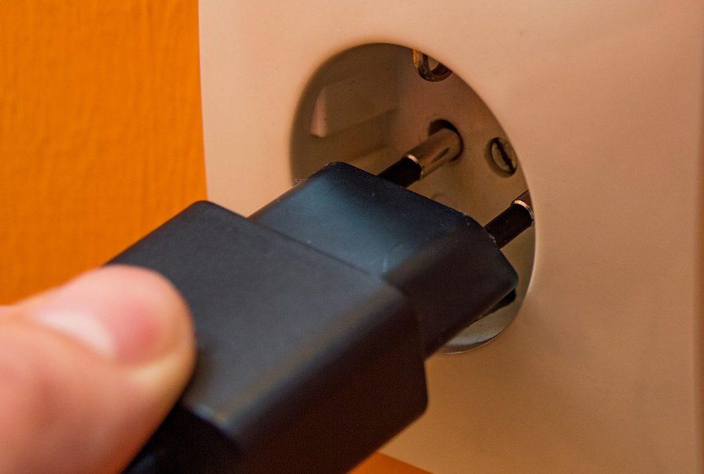 Hand steckt ein Ladegerät in Steckdose ein.