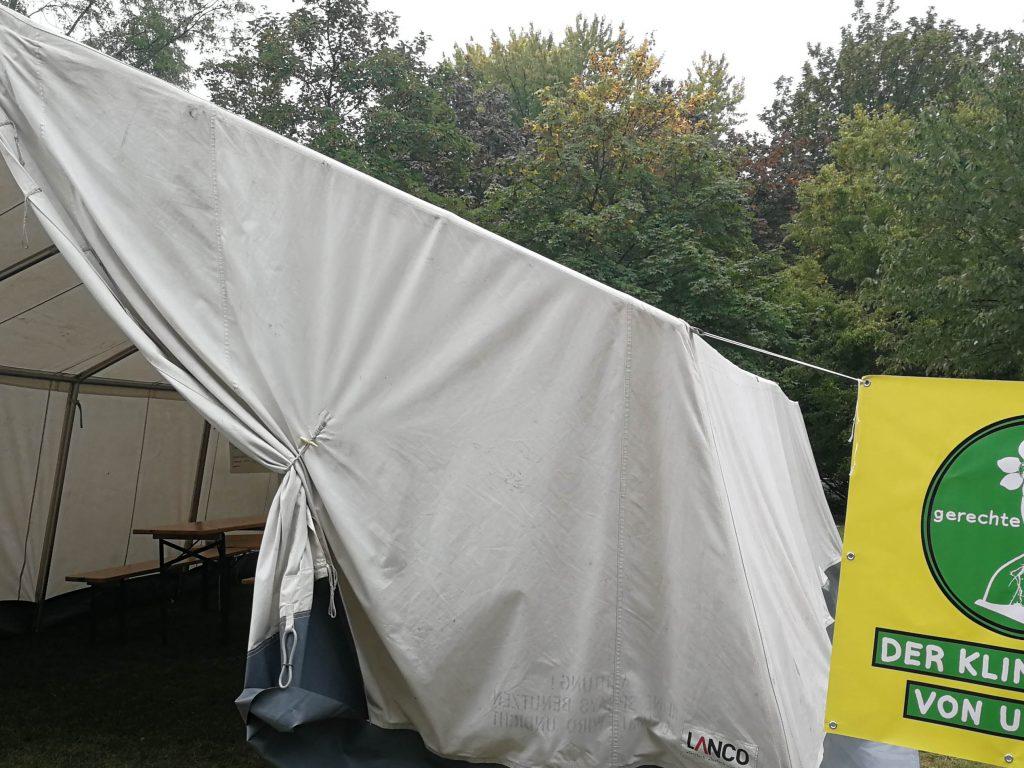 Zelt auf dem We4FutureCamp. Daneben ein gelbes Plakat mit Sanduhr und Klimaplan von unten