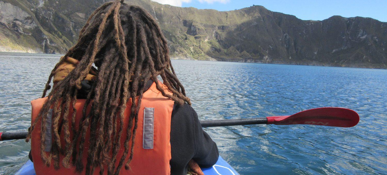 Frau paddelt in Schwimmweste übers Wasser eines Vulkankratersees