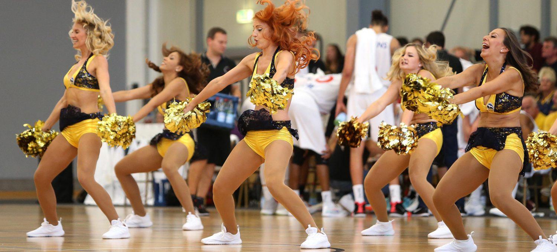 Cheerleader tanzen und ihre Haare fliegen in die Luft
