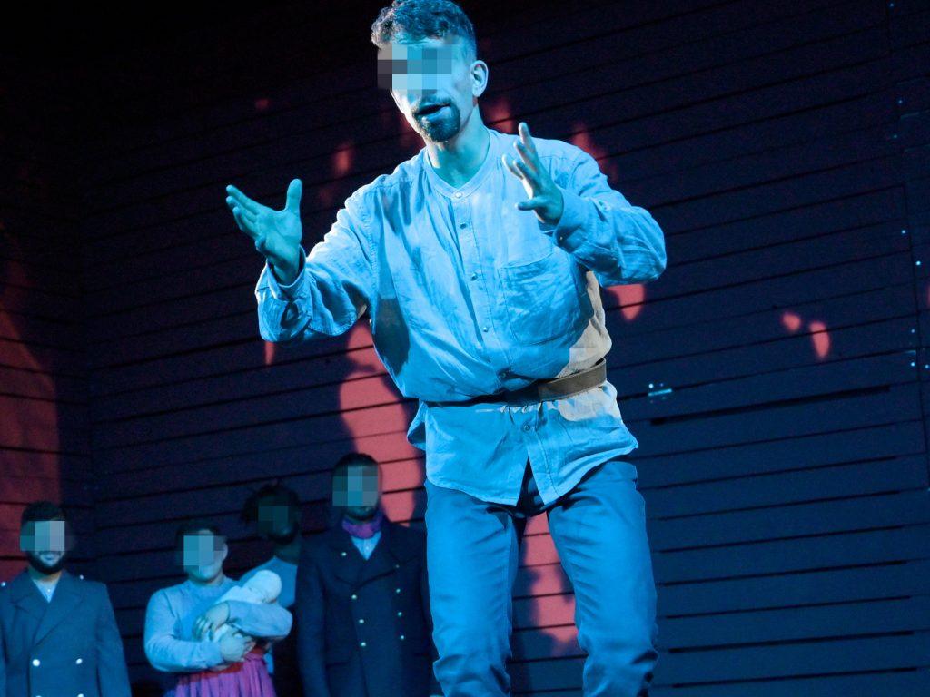 Darsteller steht erhöht auf der Bühne, weitere Schauspieler im Hintergrund.